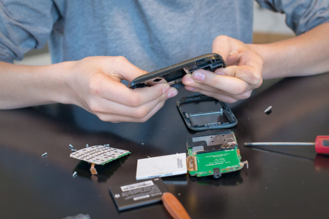 telstra - close up of hands repairing or disassembling a mobile phone